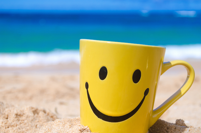 Happy face mug on the beach