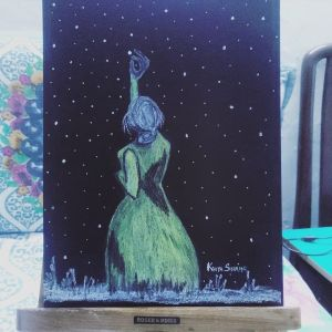 A girl reaching for the stars on a dark night